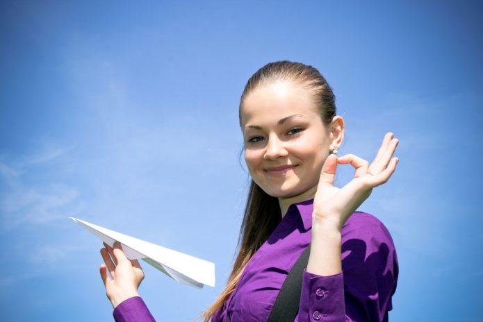 девушка с бумажным самолётом в руках на фоне синего неба