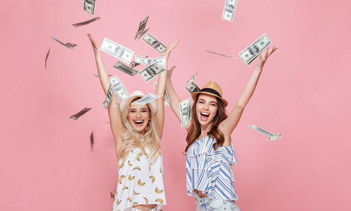 радостные девушки, летящие доллары, розовый фон