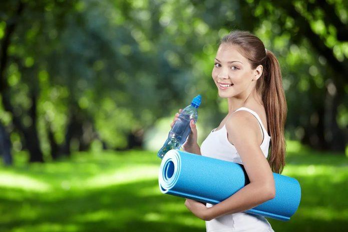 двушка со спортивным ковриков и бутылкой воды на фоне природы