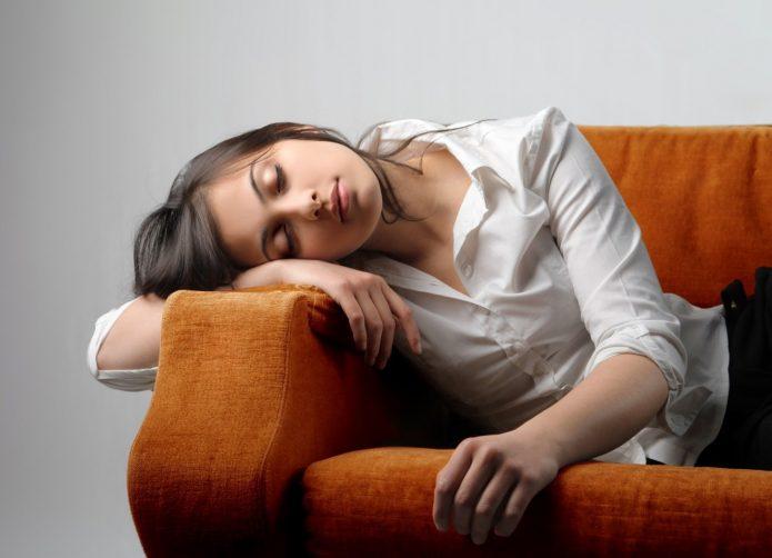 уставшая девушка на диване