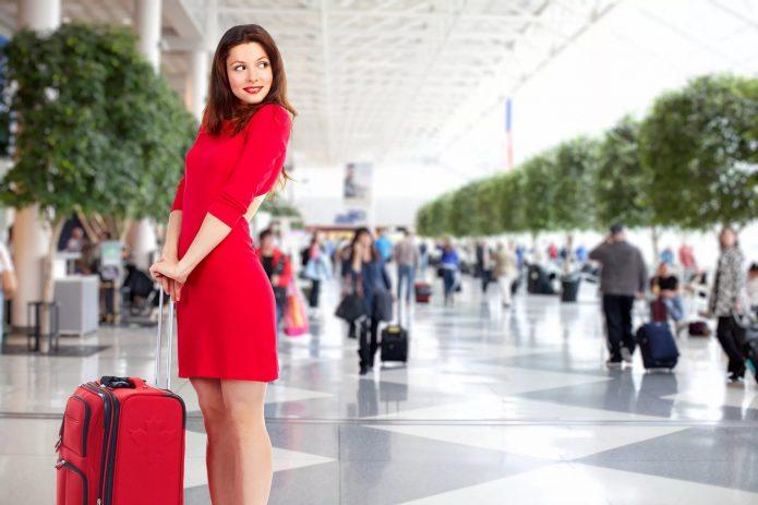 девушка в красном с чемоданом