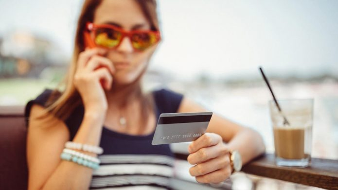 девушка с пластиковой картой и кофе, разговор по телефону