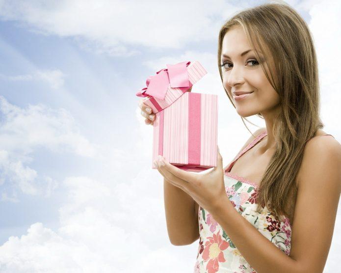 девушка с подарочной коробкой на фоне неба