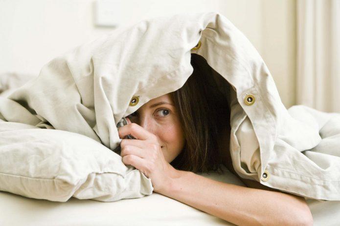 девушка прячется в постели под одеялом