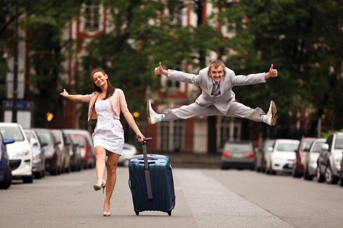 девушка с чемоданом, прыгающий парень, улица, лето, позитив