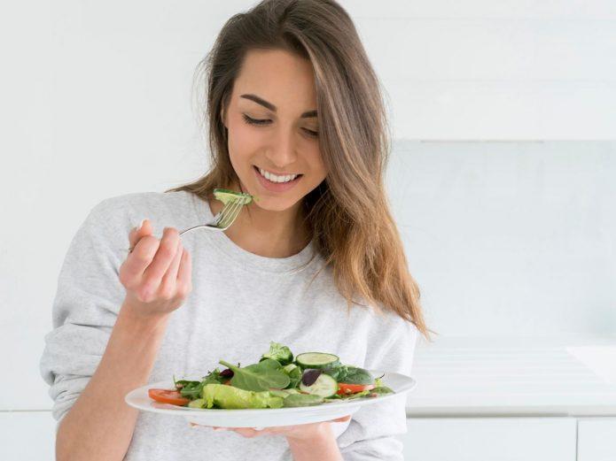 девушка есть овощной салат