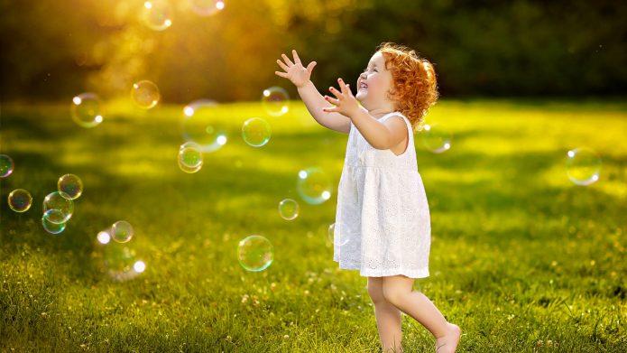 рыжая девочка, мыльные пузыри, солнце и трава