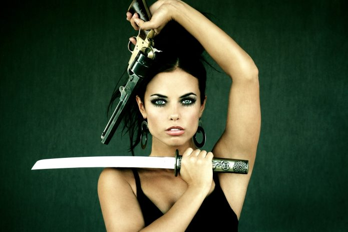 девушка с оружием на тёмно-зелёном фоне