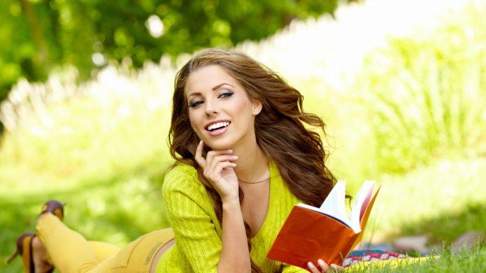 довольная успешная девушка с книгой лежит на траве
