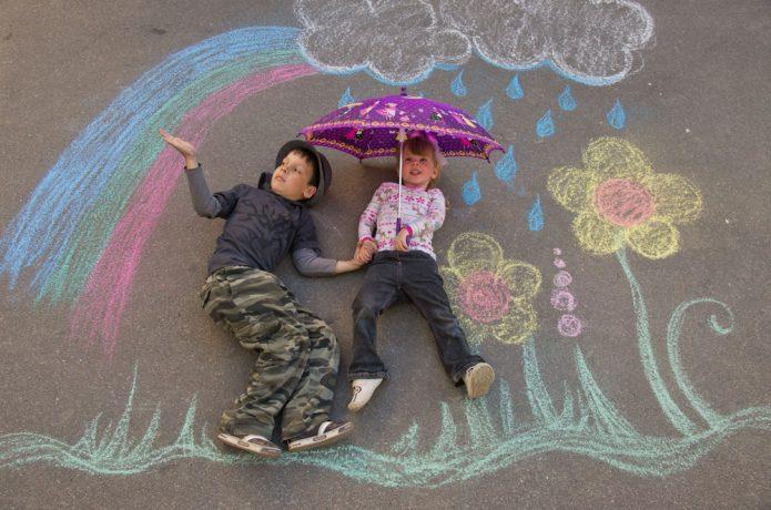 Дети лежат на асфальте рядом с нарисованными мелками картинкой