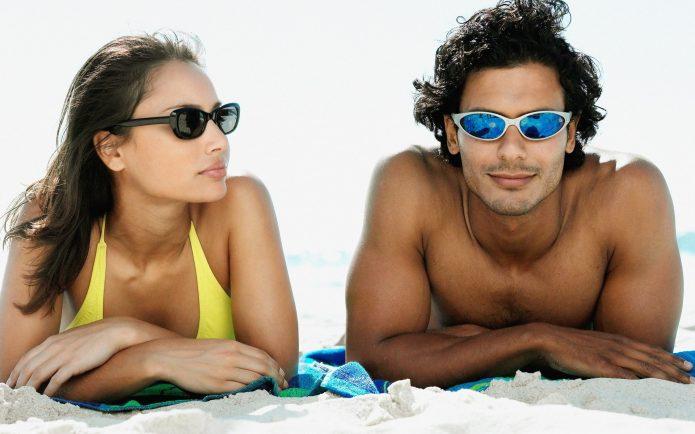 Девушка и парень в темных очках на пляже