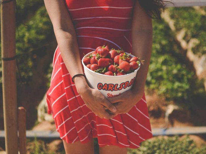 девушка в красном держит ведерко с клубникой