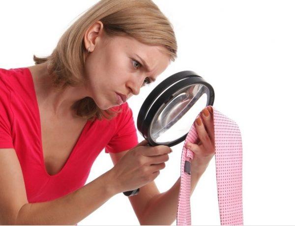 Девушка рассматривает мужской галстук через лупу