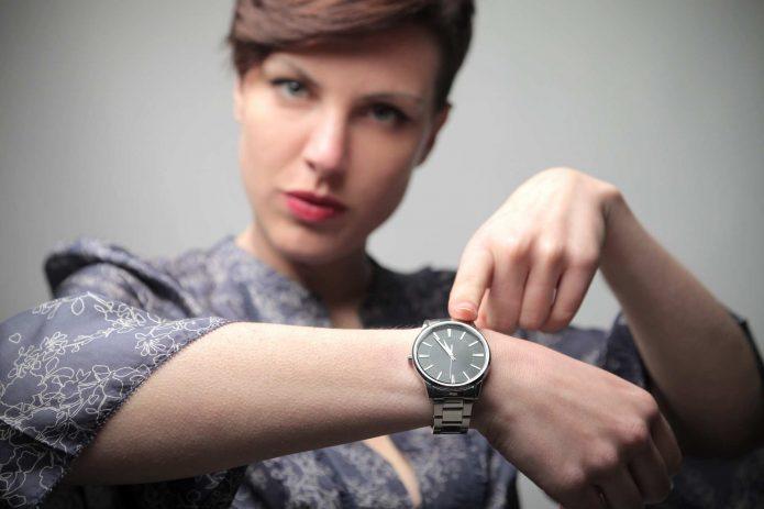 девушка указывает на наручные часы