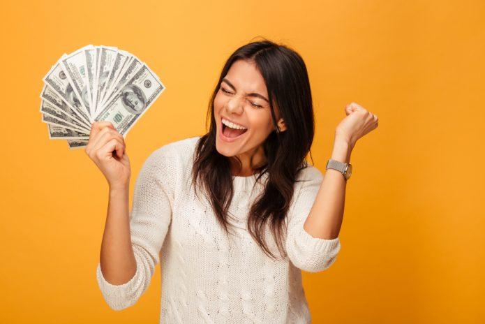 девушка на оранжевом фоне с деньгами, радость