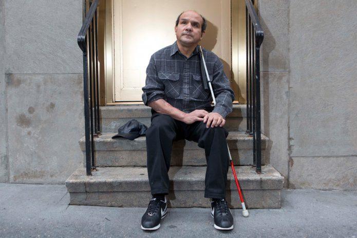 Слепой мужчина на крыльце дома