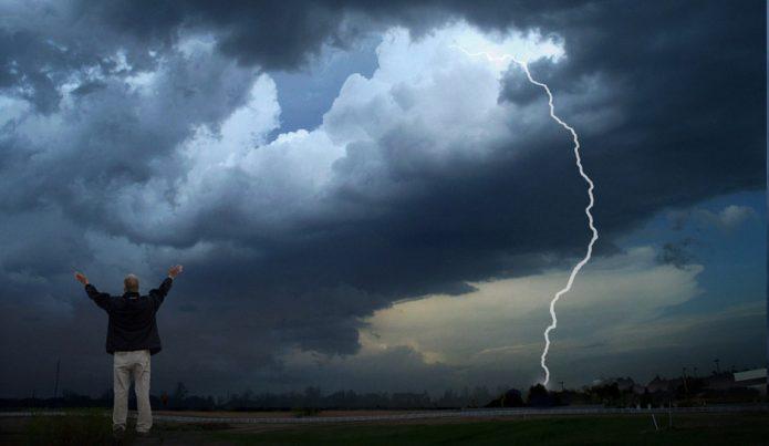 Мужчина стоит, подняв руки кверху, на фоне грозового неба