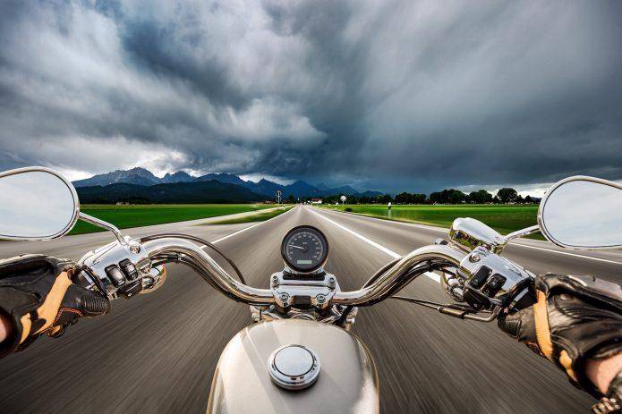 Мотоцикл на дороге и грозовое небо над ним