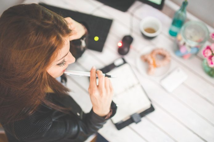 девушка с ручкой и ежедневником, компьютер, кофе и пончики