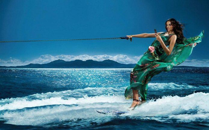 девушка с телефон в платье и на каблуках на сёрфе, волны, море