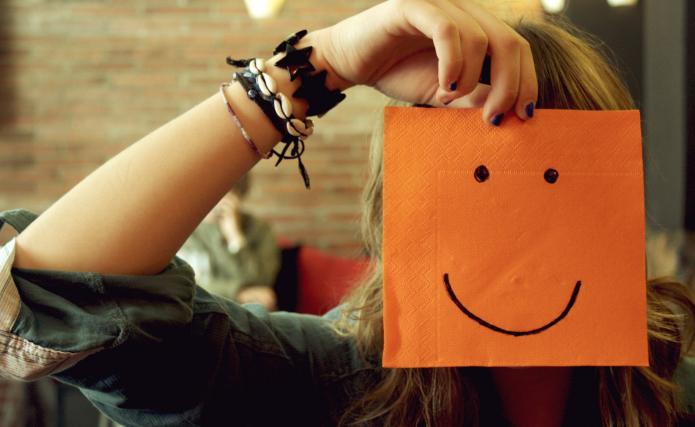 девушка прикрывает лицо салфеткой с нарисованной рожицей