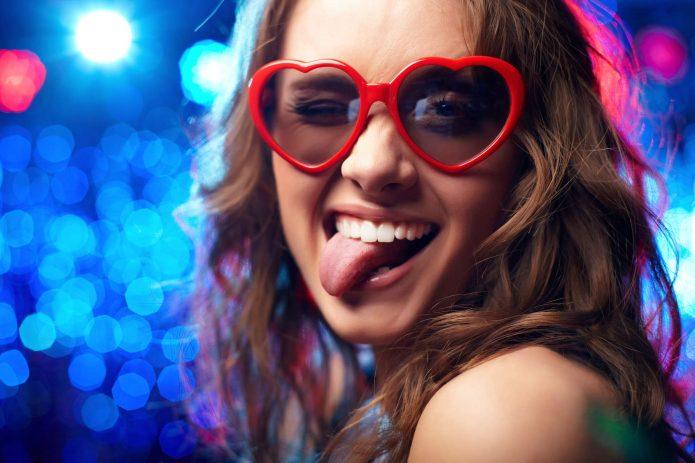 девушка в очках-сердечках показывает язык