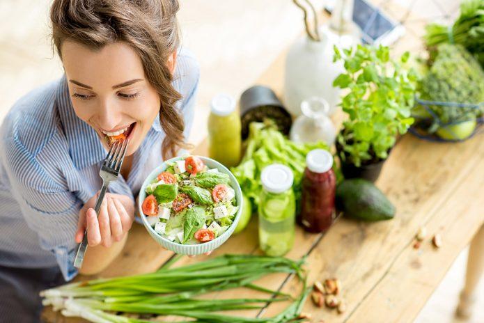 девушка есть овощной салат, овощи на столе