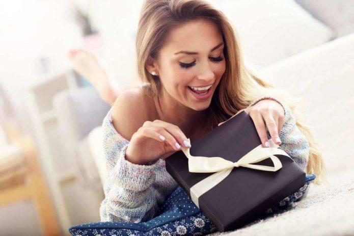 девушка разворачивает подарок, улыбка, сюрприз