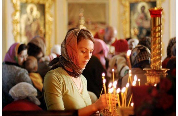 Девушка ставит свечи в церкви
