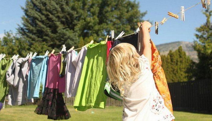 Женщина развешивает постиранное бельё