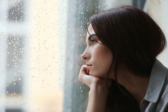грустная девушка смотрит в окно на дождь