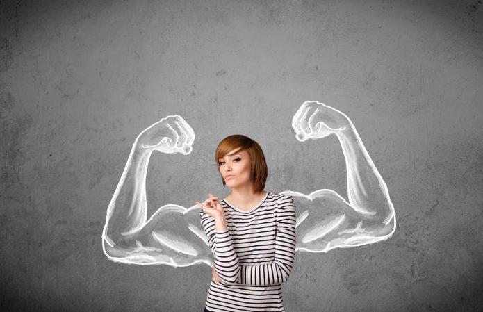 Девушка на фоне серой стены с нарисованными мускулами