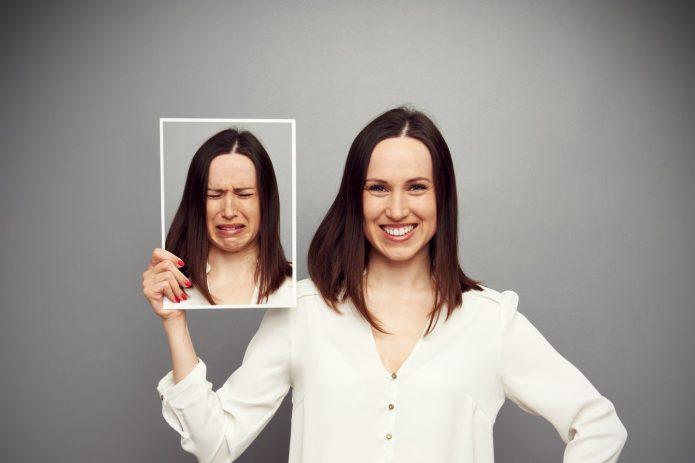 девушка улыбается, фотография с грустным лицом, серый фон