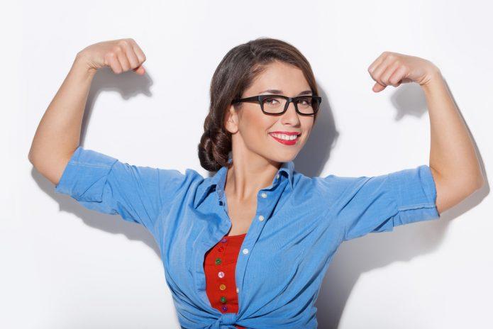 девушка в очках улыбается и показывает мускулы