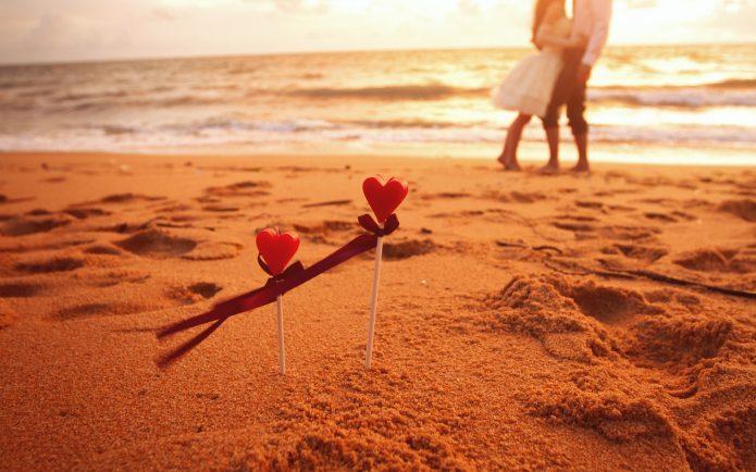 влюблённая пара, два сердечка на палочках, песчаный пляж, море