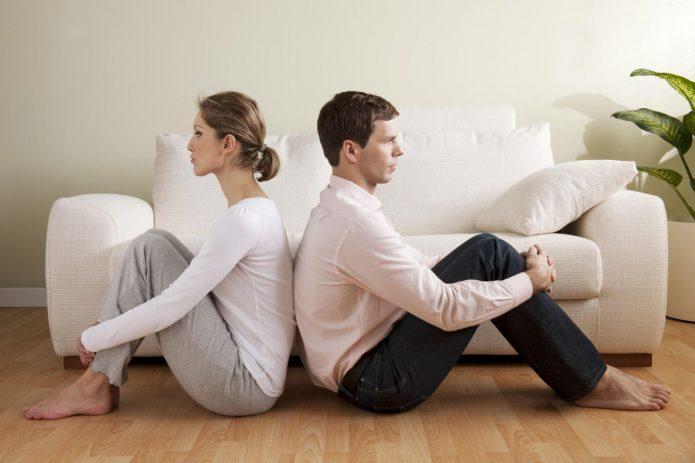 мужчина и женщина сидят на полу спиной к спине