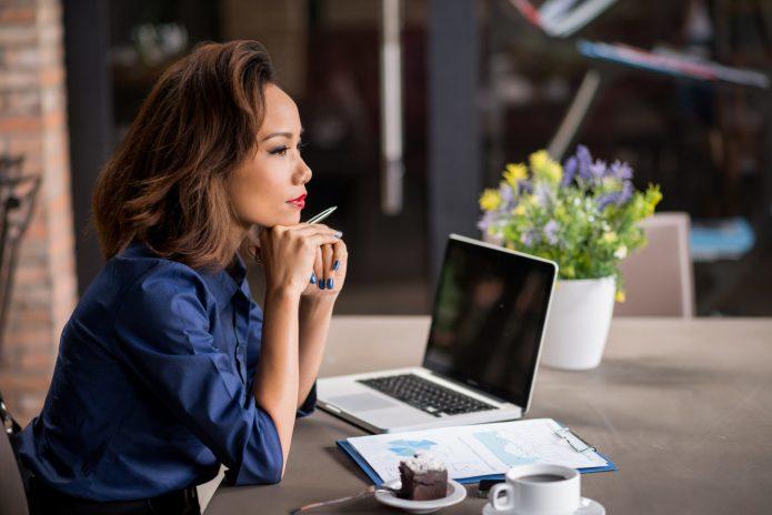 бизнес-леди за рабочим столом, ноутбук, чашка кофе, цветы