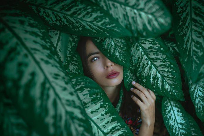 девушка прячется за зелёными листьями
