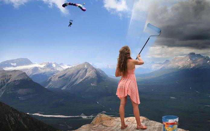 девушка красит небо на фоне гор