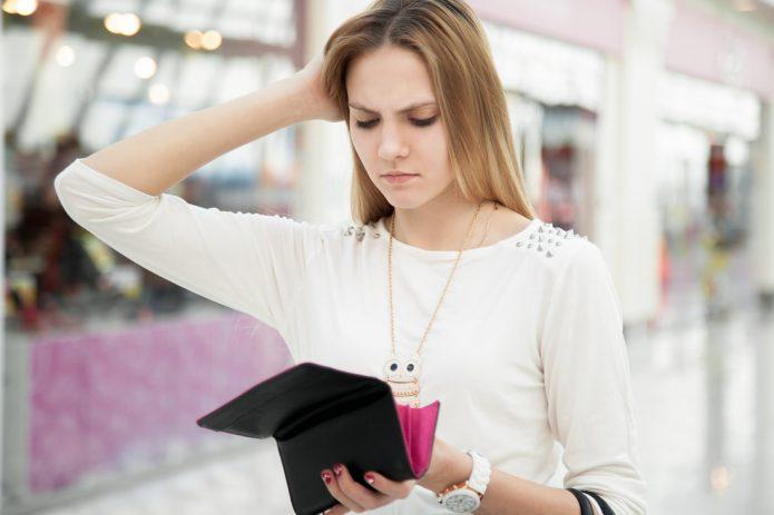 девушка задумчиво смотрит в кошелёк