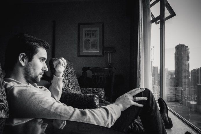 Мужчина смотрит на город за окном