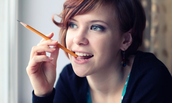 девушка держит карандаш