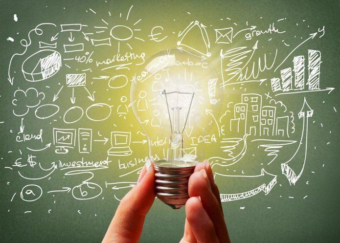 женская рука держит горящую лампочку, нарисованные идеи