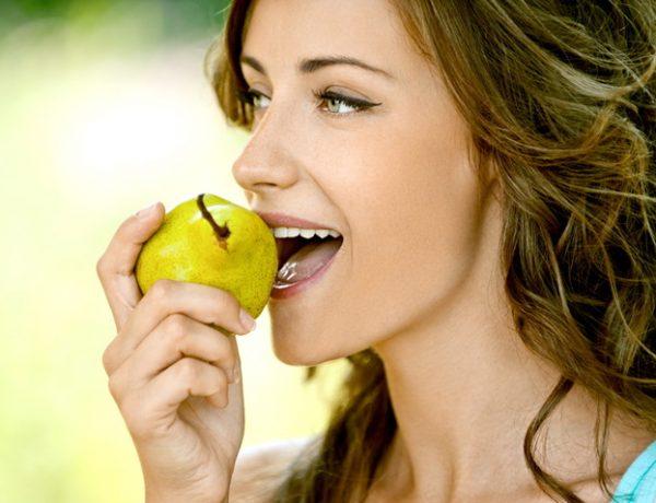 Женщина ест грушу
