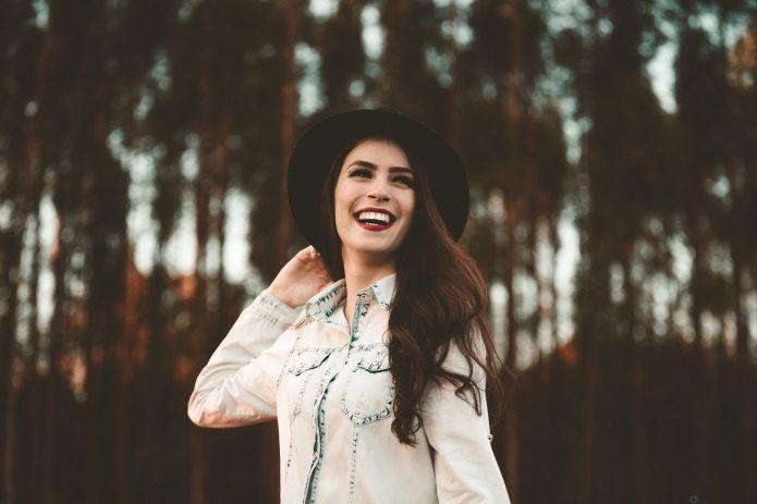 Девушка в шляпе на фоне деревьев