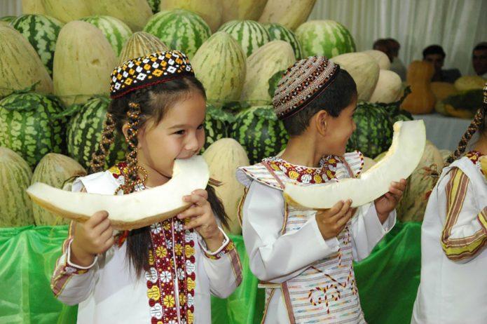 Дети в национальной одежде едят дыню