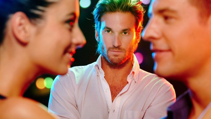 Парень смотрит на улыбающуюся другому парню девушку