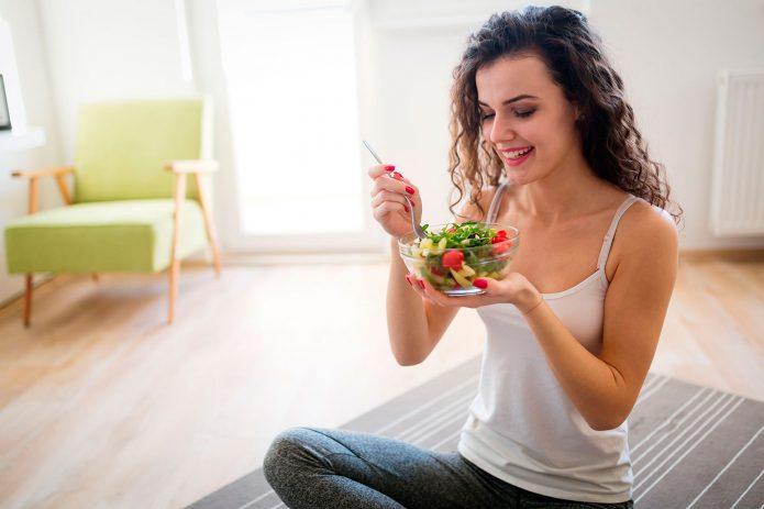 девушка ест овощной салат дома