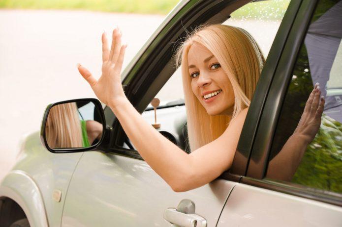 девушка в машине машет рукой