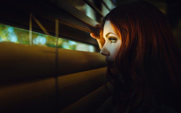 девушка подглядывает через жалюзи